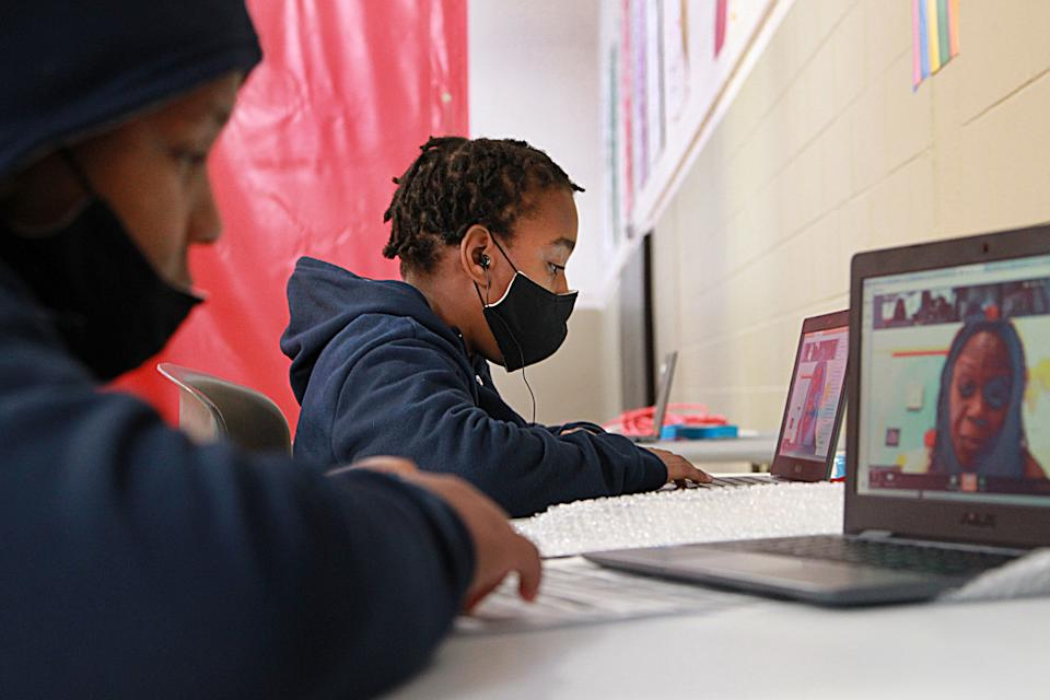 "Remote learning has ""forced many parents to leave the workforce or work from home while also supporting their children's learning."" Here, 11-year-old twins are seen participating in remote learning in Boston."