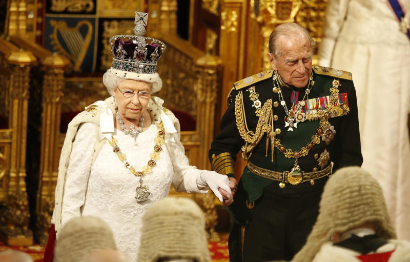 LONDON, ENGLAND - MAY 18: Prince Philip, Duke of Edinburg holds the hand of Queen Elizabeth II as they look at the assembled lawmakers after she read the Queen's Speechon from the thrown during State Opening of Parliament in the House of Lords at the Palace of Westminster on May 18, 2016 in London, England. The State Opening of Parliament is the formal start of the parliamentary year. This year's Queen's Speech, setting out the government's agenda for the coming session, is expected to outline policy on prison reform, tuition fee rises and reveal the potential site of a UK spaceport. (Photo by Alastair Grant - WPA Pool/Getty Images)