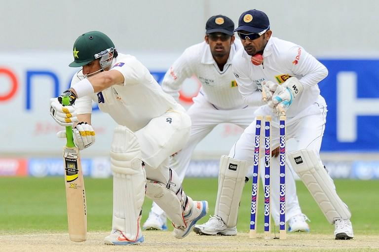 Pakistan batsman Misbah-ul-Haq (L) is bowled out as Sri Lankan wicketkeeper Prasanna Jayawardene (R) looks during the fourth day of the second cricket Test match between Pakistan and Sri Lanka at the Dubai International Cricket Stadium in Dubai on January 11, 2014.  AFP PHOTO/Ishara S. KODIKARA