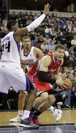 Los Angeles Clippers forward Blake Griffin, right, drives around Sacramento Kings' Jason Thompson, left, and Francisco Garcia during the first quarter of an NBA basketball game in Sacramento, Calif., Thursday, April 5, 2012. (AP Photo/Rich Pedroncelli)