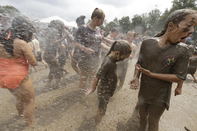 <p>Kids wash off after playing in the mud during Mud Day at the Nankin Mills Park, July 11, 2017 in Westland, Mich. (Photo: Carlos Osorio/AP) </p>