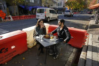Ranim Abaad and Joey Bettencourt, right, have lunch at the RIND in Sacramento, Calif., Friday, Nov. 20, 2020. The city has put up protective barricades in street parking areas to allow restaurants to space out the dining areas to follow social distancing guidelines due to the COVID-19 pandemic. California on Saturday will join other states in trying a partial overnight curfew to stem a surge in coronavirus cases. The curfew from 10 p.m. to 5 a.m. will force some eateries to shorten their hours of operations, although restaurants can stay open for takeout and delivery after 10 p.m. (AP Photo/Rich Pedroncelli)