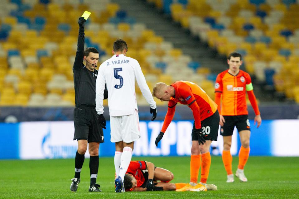 KHARKOV, UKRAINE - DECEMBER 01: (BILD ZEITUNG OUT) referee Ovidiu Hategan gives Raphael Varane of Real Madrid the yellow card during the UEFA Champions League Group B stage match between Shakhtar Donetsk and Real Madrid at Metalist Stadium on December 1, 2020 in Kharkov, Ukraine. (Photo by Stanislav Vedmid/DeFodi Images via Getty Images)