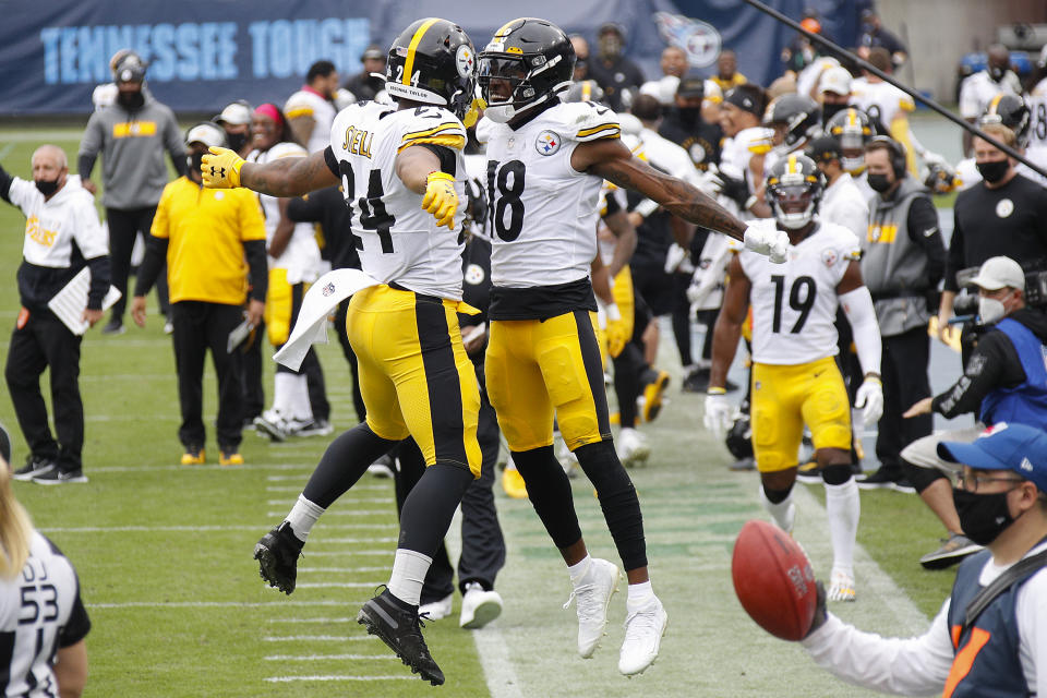 Benny Snell and Diontae Johnson bump chests in the air on the Steelers sideline.