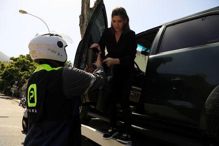 An employee of Pana, a mobile application which dispatches security crews to stranded drivers who request help, assists Vanessa Mikuski to get off a towing truck in Caracas, Venezuela June 15, 2018. Picture taken June 15, 2018. REUTERS/Adriana Loureiro