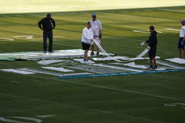 People prepare to paint the field during a tour of the Hard Rock Stadium on Tuesday, Jan. 21, 2020, ahead of the NFL Super Bowl LIV football game in Miami Gardens, Fla. (AP Photo/Brynn Anderson)