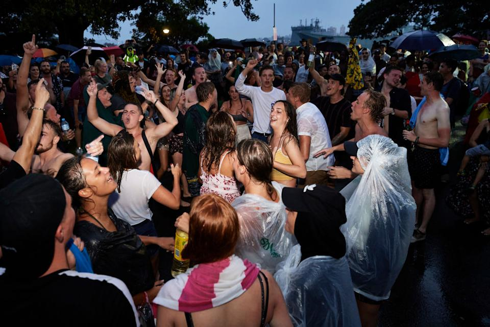 Crowds brave the rain and continue to party before the firework display on New Year's Eve on Sydney Harbour in December 2018.