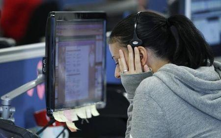 A worker on IG Index's trading floor puts her hand to her face as she speask on the phone while markets tumble, in London