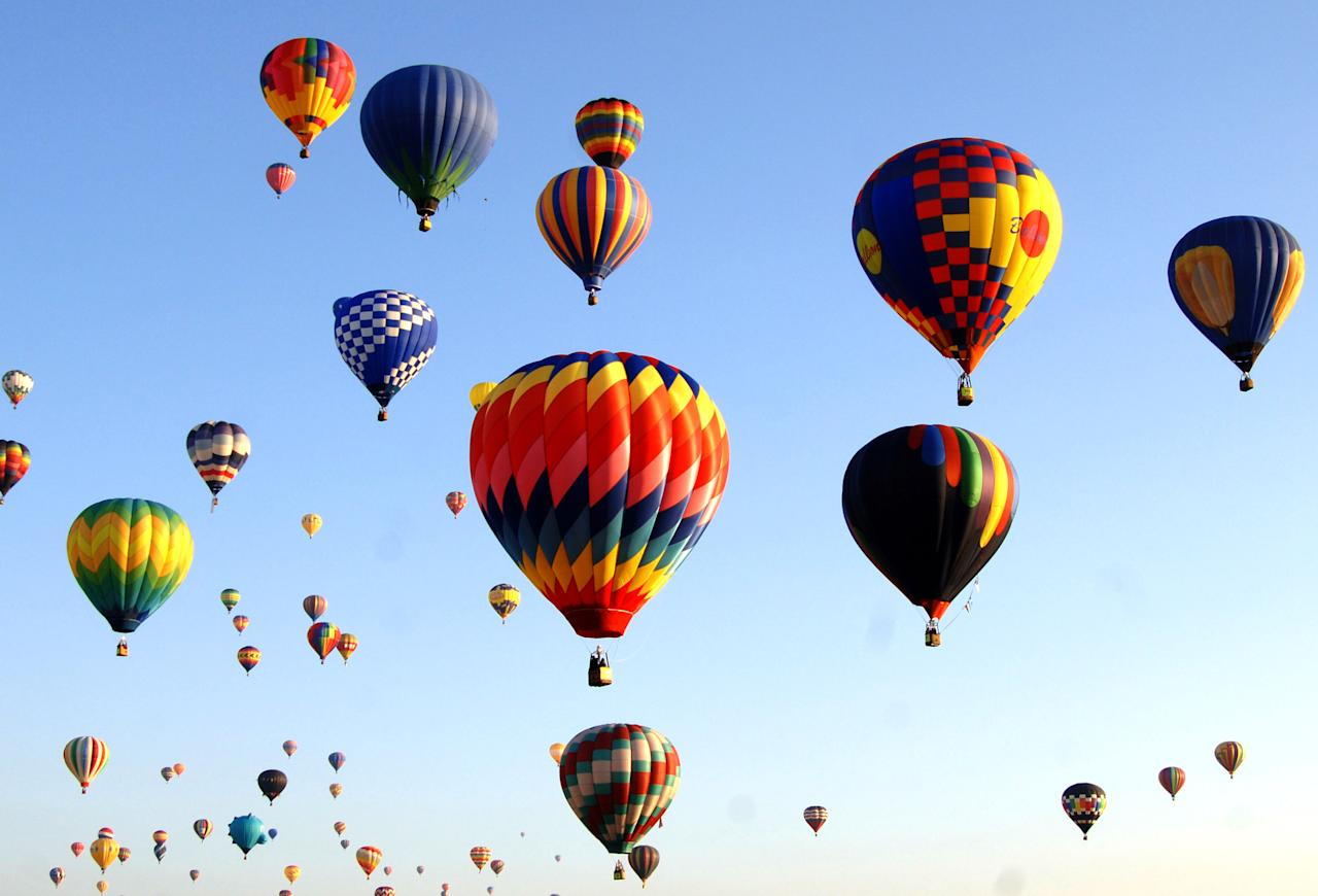 Hot air balloons fly overhead during a morning ascent at the Albuquerque International Balloon Fiesta in Albuquerque, New Mexico on October 8, 2005. (Photo by A. Messerschmidt/Getty Images)