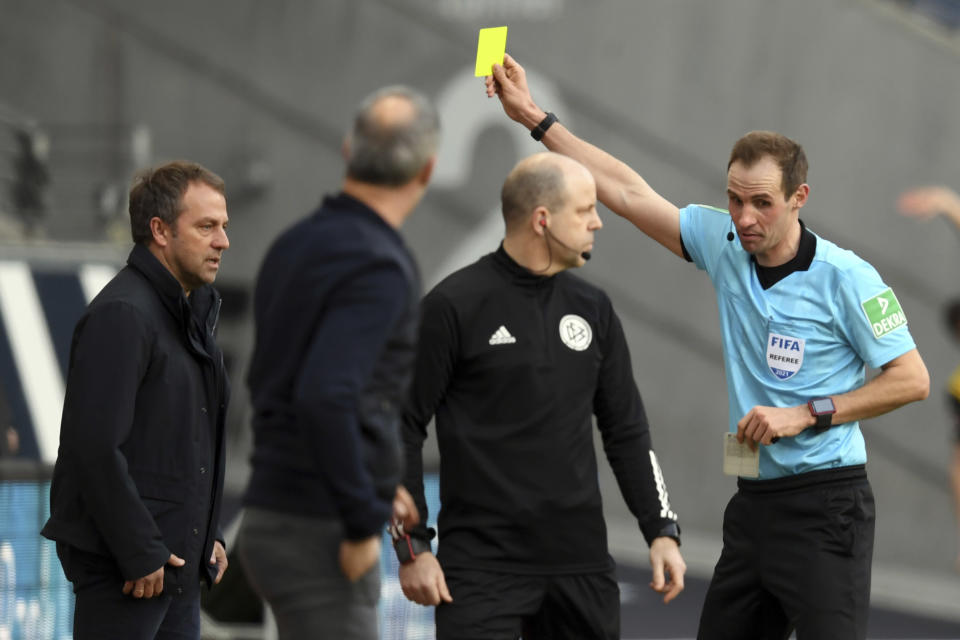 Referee Sascha Stegemann, right, shows Munich coach Hansi Flick, left, the yellow card during the German Bundesliga soccer match between Eintracht Frankfurt and Bayern Munich in Frankfurt, Germany, Saturday, Feb. 20, 2021. (Arne Dedert/POOL via AP)