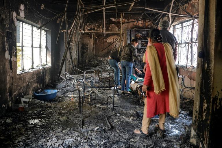 People inspect the remains of a burnt-out school premises following clashes between people supporting and opposing a contentious amendment to India's citizenship law, in New Delhi