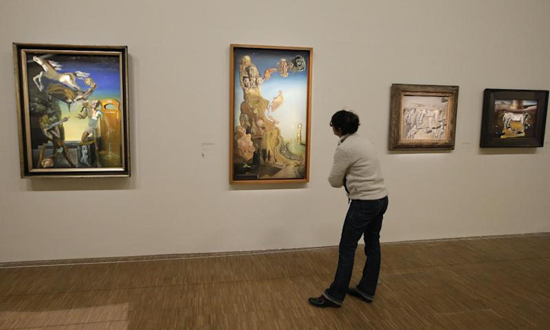 """In this photo taken Monday Nov. 19, 2012, a woman looks at the painting 'La memoire de la femme enfant, 1929', second left, by Spanish artist Salvador Dali (1904-1989) during the presentation to the press of the exhibition """"Dali"""" at the Centre Pompidou modern art museum, in Paris. A major retrospective of Salvador Dali in Paris aims to rewrite the art history books, reconciling for the first time the last decades of his life _ when he was accused of money-making self-publicity through numerous television appearances _ with his earlier, respected Surrealist period. (AP Photo/Francois Mori)"""