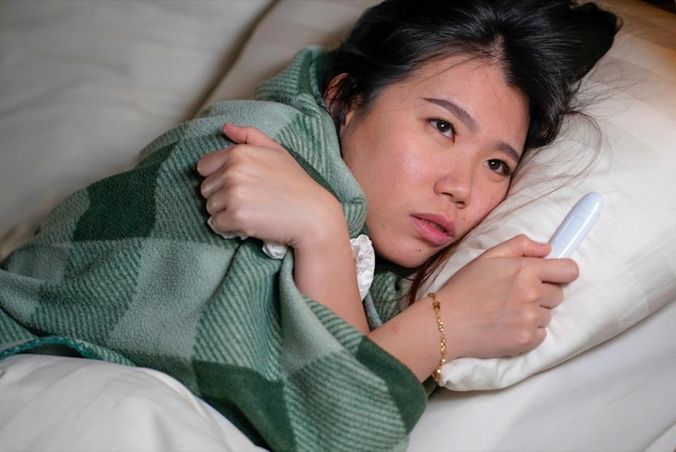 woman lying on bed at home sick suffering cold flu and temperature covered with blanket feeling unwell and feverish