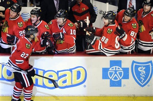 Chicago Blackhawks' Johnny Oduya left, celebrates with teammates after scoring against the New York Rangers during the third period of an NHL hockey game in Chicago, Friday, March 9, 2012. Chicago won 4-3. (AP Photo/Paul Beaty)