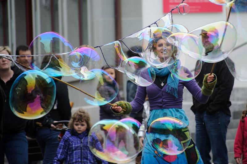 A woman blows giant bubbles in a street in the town of Appenzell, eastern Switzerland on April 28, 2013 (AFP Photo/Sebastien Bozon)