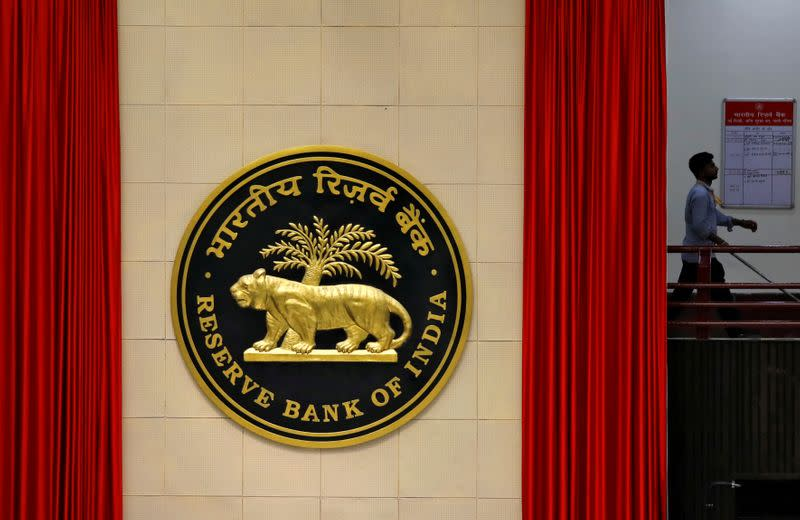 FILE PHOTO: A worker walks past the logo of Reserve Bank of India inside its office in New Delhi