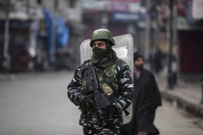 An Indian paramilitary soldier patrols through a closed market in Srinagar, Indian controlled Kashmir, Tuesday, Feb. 9, 2021. Businesses and shops have closed in many parts of Indian-controlled Kashmir to mark the eighth anniversary of the secret execution of a Kashmiri man in New Delhi. Hundreds of armed police and paramilitary soldiers in riot gear patrolled as most residents stayed indoors in the disputed region's main city of Srinagar. (AP Photo/Mukhtar Khan)