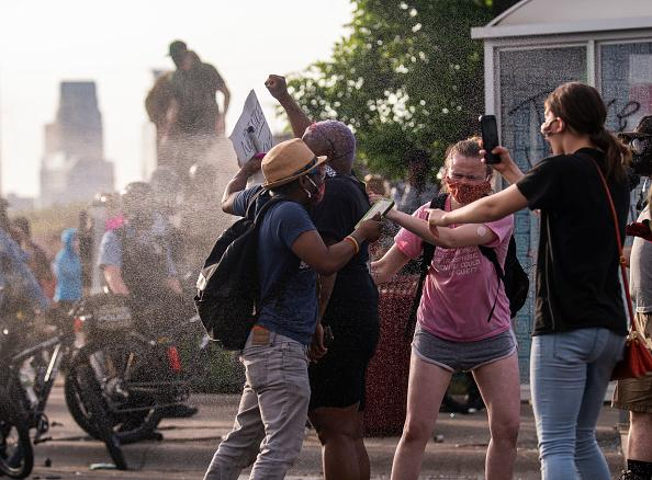 Protesters are shot with pepper spray as they confront police outside the Third Police Precinct in Minneapolis, Minnesota.