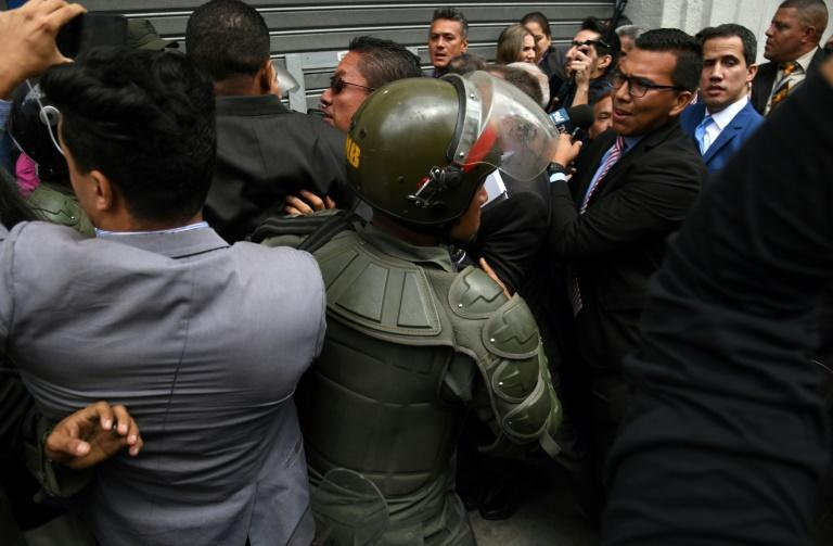 Venezuelan opposition leader and self-proclaimed acting president Juan Guaido (R, blue suit) heads towards the entrance of the National Assembly while journalists struggle with Bolivarian National Guard after being banned from entering (AFP Photo/Yuri CORTEZ)