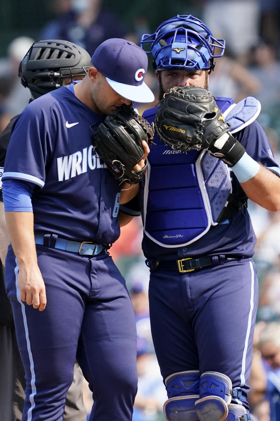 Chicago Cubs catcher Austin Romine, right, talks with relief pitcher Ryan Meisinger in the eighth inning of a baseball game against the Kansas City Royals, Friday, Aug. 20, 2021, in Chicago. (AP Photo/Nam Y. Huh)