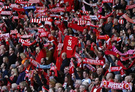 Fans hold up scarves during a memorial service to mark the 25th anniversary of the Hillsborough disaster at Anfield in Liverpool, northern England April 15, 2014. REUTERS/Darren Staples