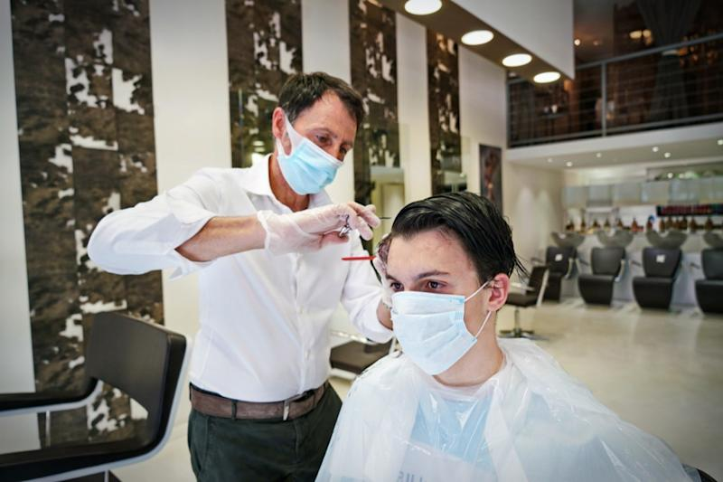 A hairdresser, wearing a protective face mask, works in a barber shop