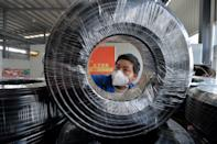 A worker wearing a face mask works on a production line manufacturing cables at a factory in Guiyang, Guizhou province, China February 25, 2020. Picture taken February 25, 2020. China Daily via REUTERS ATTENTION EDITORS - THIS IMAGE WAS PROVIDED BY A THIRD PARTY. CHINA OUT.
