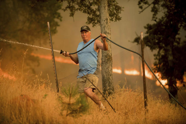 <p>Jim Berglund sprays water while defending his home as a wildfire approaches on Saturday, July 8, 2017, near Oroville, Calif. Although flames leveled Berglund's barn, his home remained unscathed as the main fire head passed. (AP Photo/Noah Berger) </p>