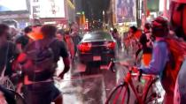 A car drives through a crowd of people during a protest in New York