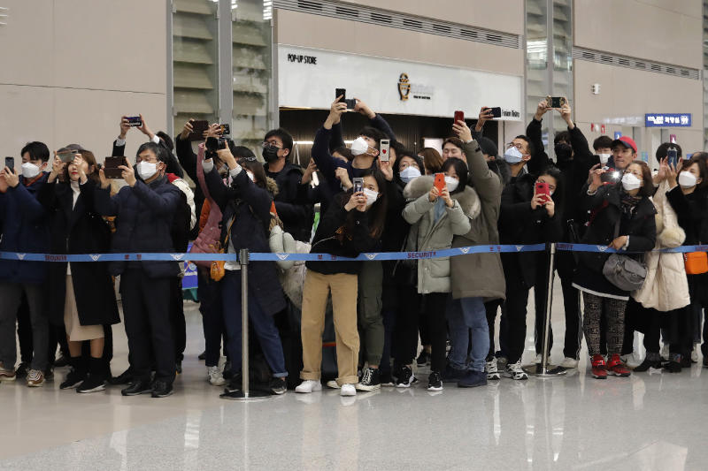 """People take photos of South Korean director Bong Joon-ho upon his arrival at the Incheon International Airport in Incheon, South Korea, Sunday, Feb. 16, 2020. South Koreans are reveling in writer-director Bong's dark comic thriller, """"Parasite,"""" which won this year's Academy Awards for best film and best international feature. The movie itself, however, doesn't put the country in a particularly positive light. (AP Photo/Ahn Young-joon)"""