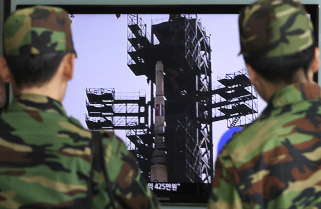 South Korean Army soldiers watch a TV news program which shows North Korea's Unha-3 rocket at Seoul train station in Seoul, South Korea, Monday, April 9, 2012. North Korean space officials moved all three stages of the long-range rocket into position for a controversial launch, vowing Sunday to push ahead with their plan in defiance of international warnings against violating a ban on missile activity. (AP Photo/Ahn Young-joon)