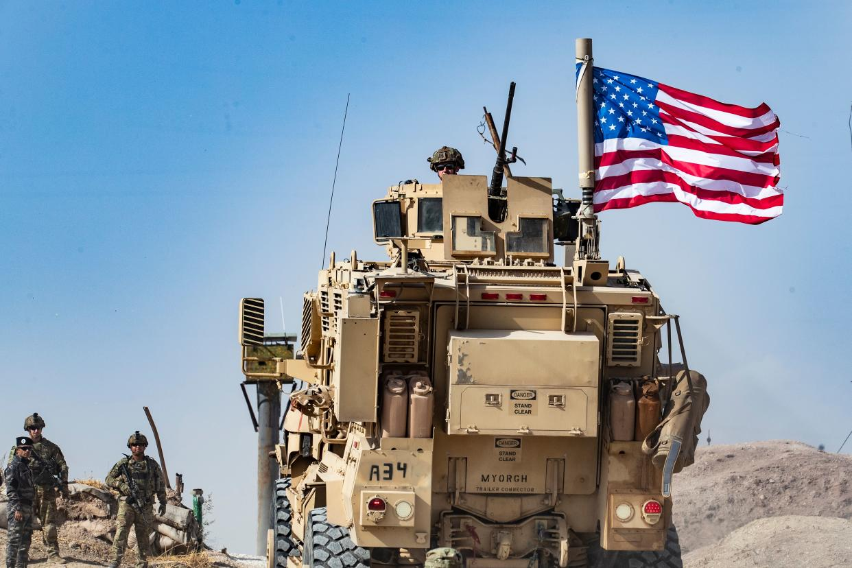 A U.S. soldier sits atop an armored vehicle during a demonstration on Sunday by Syrian Kurds against Turkish threats. (Photo: Delil Souleiman/AFP/Getty Images)