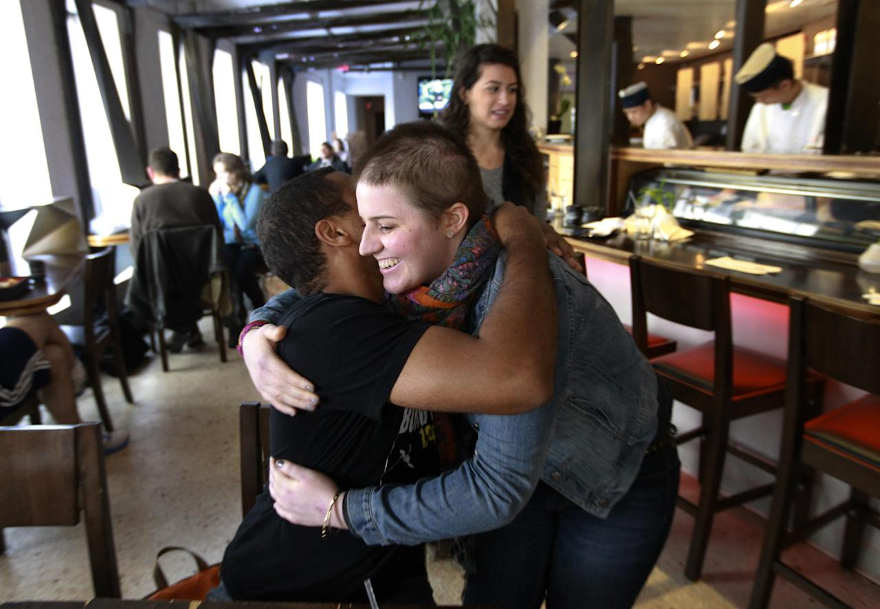 In this Thursday, Oct. 25, 2012 photo, Boston University senior Dustin Holstein, of Southborough, Mass., left, hugs his friend Meg Theriault during a chance meeting at a restaurant near the BU campus in Boston. Holstein was an eyewitness to a multi-fatal minivan accident where Meg nearly died. Holstein was driving a different minivan and saw the crash in his mirror. (AP Photo/Steven Senne)