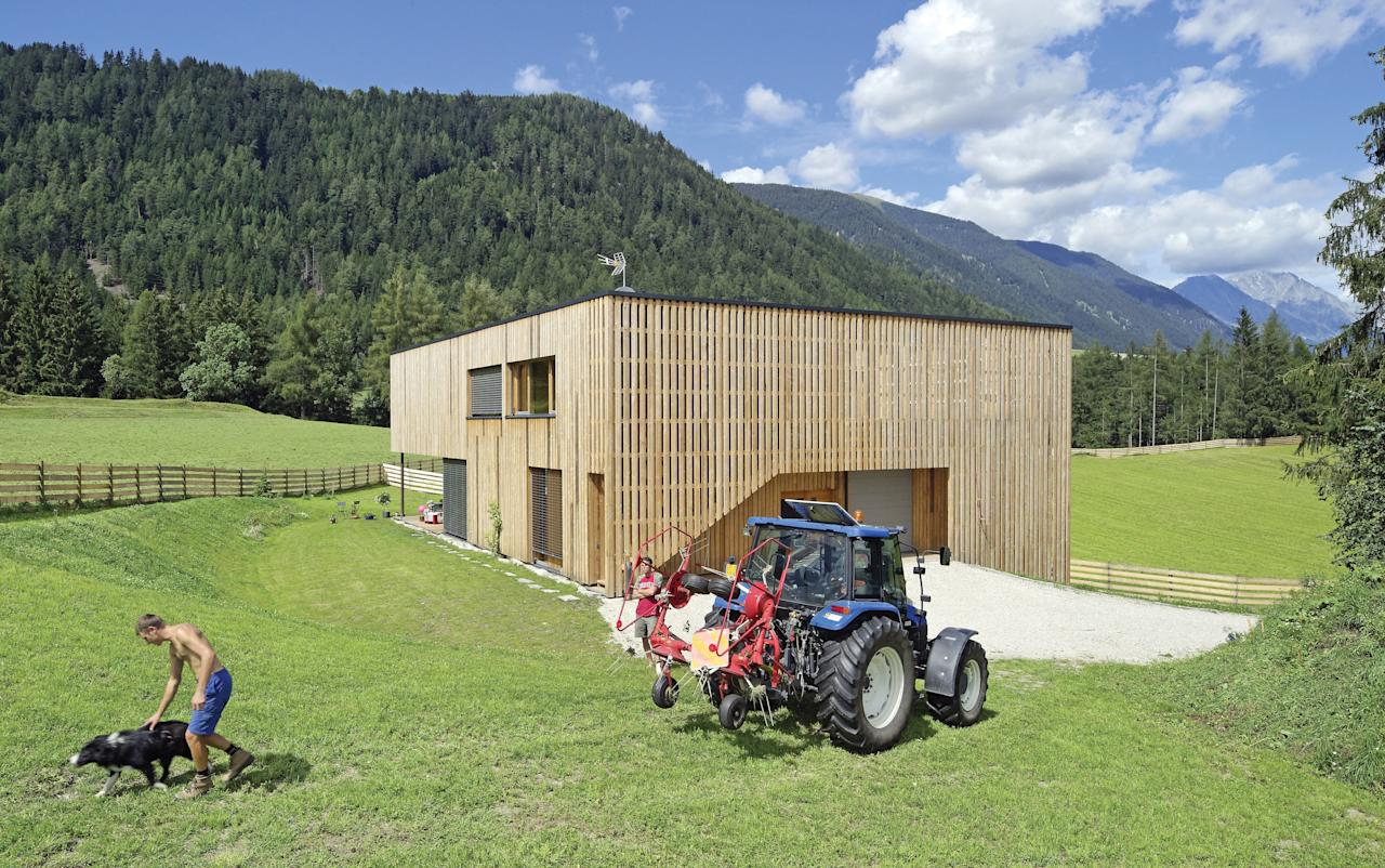 On a 21-acre farm in the Dolomites, architect Reinhard Madritsch created a structure that could serve as a home for the Prugger family and a barn for their Scottish Highland cattle. The cubic building is wrapped in vertical strips of wood and set into a hillside, creating separate levels for living and working.