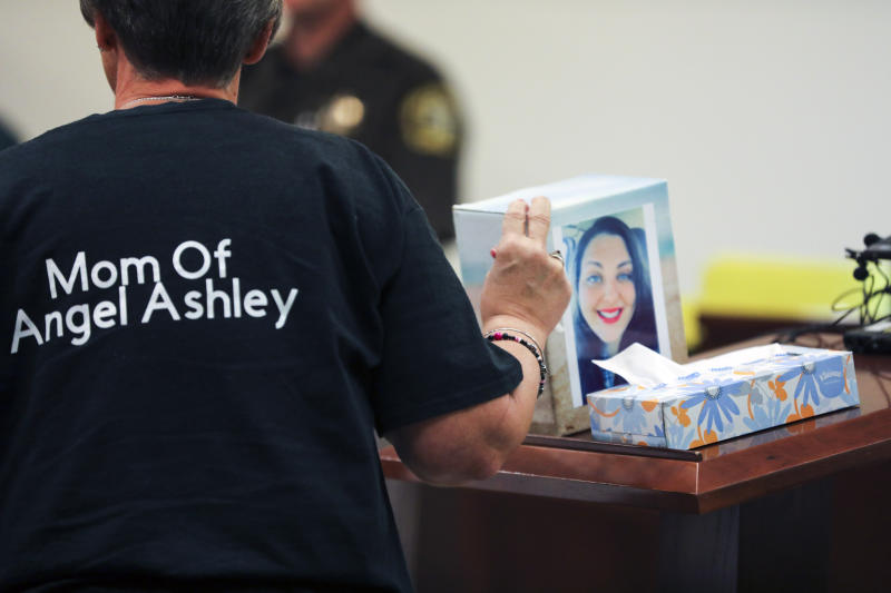 "Kristine Young, mother of Ashley Young, gestures to a box containing her daughter's ashes during the sentencing of Jared Chance in Kent County Circuit Court,  Thursday, Oct. 10, 2019, in Grand Rapids, Mich. Chance, a Michigan man convicted of killing and dismembering Ashley Young has been sentenced to at least 100 years in prison after a judge called his actions ""reprehensible and heinous.""(Brian Hayes/The Grand Rapids Press via AP)"