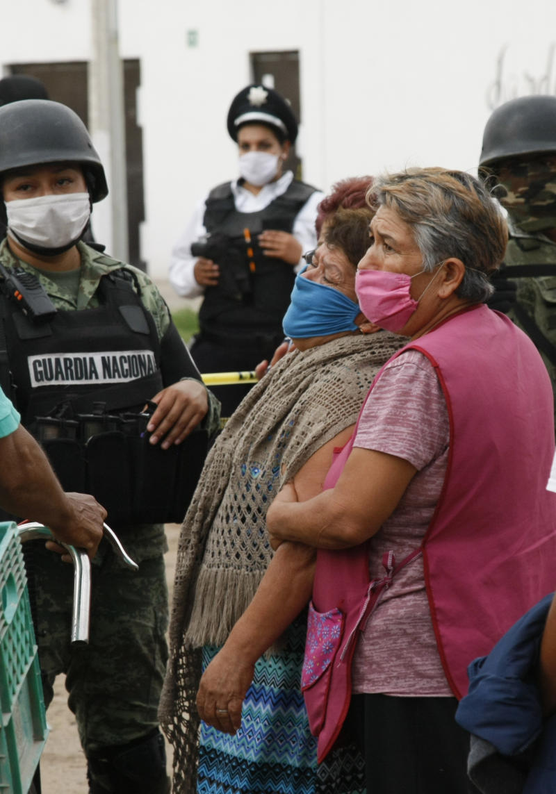 Relatives of the victims of a shooting at an unregistered drug rehabilitation center wait in anguish outside the rehab center in Irapuato, Mexico, Wednesday, July 1, 2020. Gunmen burst into the center and opened fire, killing more than 20 and wounding several more. (AP Photo/Mario Armas)