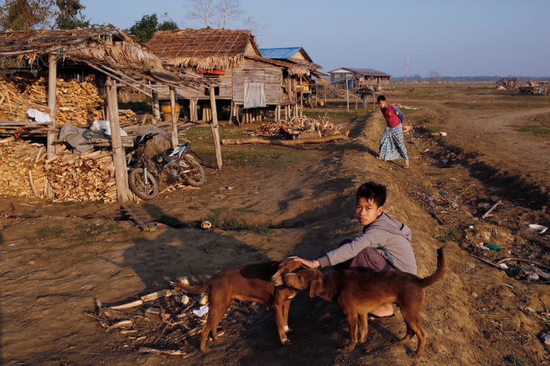 A boy from Ta Dar U village pets a dog after villagers relocated their houses inland in Bago, Myanmar