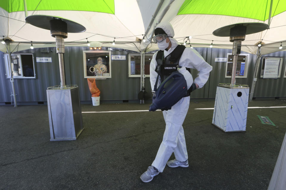 A worker wearing protective suits sprays disinfectant as a precaution against the coronavirus at a makeshift clinic in Seoul, South Korea, Saturday, Jan. 2, 2021. South Korea is extending stringent distancing rules for two more weeks as authorities seek to suppress a viral resurgence, while confirming its first case of an apparently more contagious coronavirus variant detected in South Africa. (AP Photo/Ahn Young-joon)