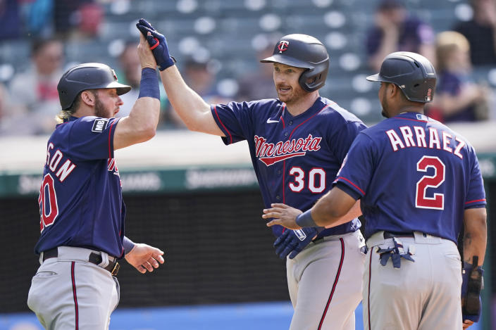 Minnesota Twins' Kyle Garlick (30) celebrates with Minnesota Twins' Josh Donaldson and Luis Arraez after hitting a three-run home run in the tenth inning of a baseball game against the Cleveland Indians, Sunday, May 23, 2021, in Cleveland. (AP Photo/Tony Dejak)