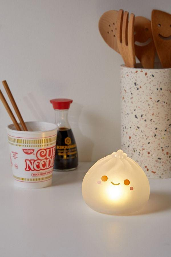 """<p>Who wouldn't smile upon receiving this <a href=""""https://www.popsugar.com/buy/Smoko-UO-Exclusive-Dumpling-Light-511496?p_name=Smoko%20UO%20Exclusive%20Dumpling%20Light&retailer=urbanoutfitters.com&pid=511496&price=16&evar1=savvy%3Auk&evar9=46695667&evar98=https%3A%2F%2Fwww.popsugar.com%2Fsmart-living%2Fphoto-gallery%2F46695667%2Fimage%2F46850664%2FSmoko-UO-Exclusive-Dumpling-Light&list1=shopping%2Cgifts%2Curban%20outfitters%2Cgift%20guide&prop13=api&pdata=1"""" rel=""""nofollow"""" data-shoppable-link=""""1"""" target=""""_blank"""" class=""""ga-track"""" data-ga-category=""""Related"""" data-ga-label=""""https://www.urbanoutfitters.com/shop/smoko-uo-exclusive-dumpling-light?category=PRODUCTTRAY&amp;color=100"""" data-ga-action=""""In-Line Links"""">Smoko UO Exclusive Dumpling Light</a> ($16)?</p>"""