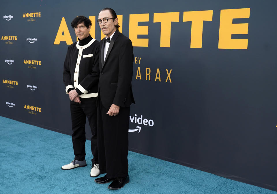 """Russell Mael, left, and his brother Ron of the band Sparks pose together at a special screening of the film """"Annette"""" at the Hollywood Forever Cemetery, Aug. 18, 2021 - Credit: Chris Pizzello/Invision/AP"""