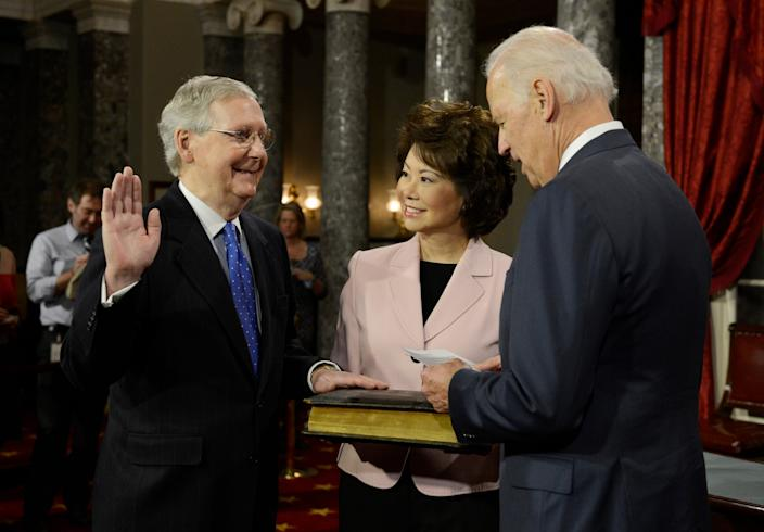 Sen. Mitch McConnell, R-Ky., participates in a ceremonial swearing-in performed by Vice President Biden in the Old Senate Chamber at the U.S. Capitol in Washington on Jan. 6, 2015. McConnell's wife Elaine Chao is beside him. Senators were officially sworn-in on the Senate floor earlier in the day.