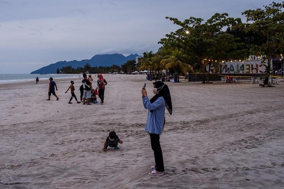 Tourists and local residents spend their leisure time at Pantai Cenang in Langkawi September 15, 2021.