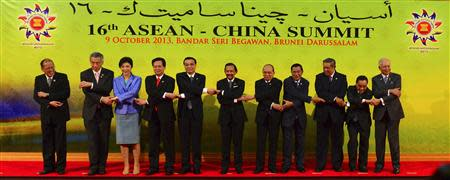 ASEAN leaders and China's Premier Li link hands as they pose for a group photo at the 16th ASEAN-China Summit in Bandar Seri Begawan