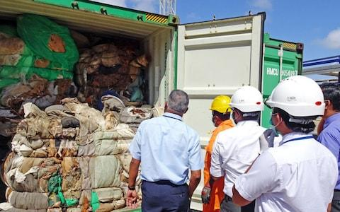 Customs officials inspect one of the abandoned containers, which have been arriving at the port over the past two years - Credit: AFP