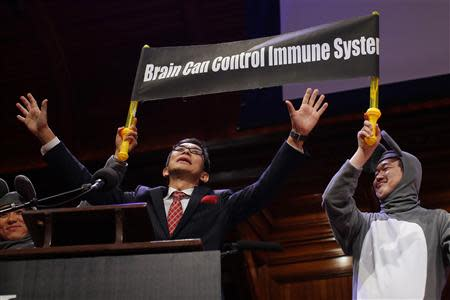 Masanori Niimi is joined by colleague Xiangyuan Jin, dressed as a mouse, as they accept the 2013 Medicine Prize during the 23rd First Annual Ig Nobel Prize ceremony at Harvard University in Cambridge
