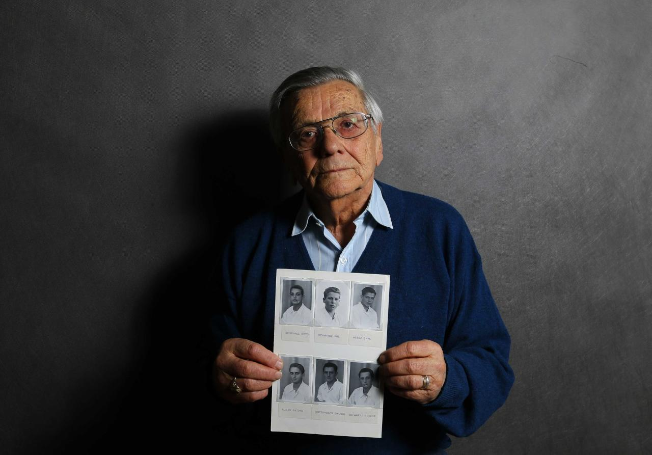 Auschwitz death camp survivor Imre Varsanyi, 86, holds up a photo of fellow survivors during World War Two, as he poses for a portrait in Budapest January 12, 2015. Varsanyi was 14-years-old when he and his family were sent to Auschwitz-Birkenau. He was the only member of his family to survive. After the war Varsanyi did not talk about Auschwitz for 60 years because he felt ashamed of having survived. As the liberation of Auschwitz approaches its 70th anniversary this month, Reuters photographers took portraits of now elderly survivors. About 1.5 million people, most of them Jews, were killed at the Nazi camp which has became a symbol of the horrors of the Holocaust and World War Two, which ravaged Europe. The camp was liberated by Soviet Red Army troops on January 27, 1945 and about 200,000 camp inmates survived. REUTERS/Laszlo Balogh (HUNGARY - Tags: ANNIVERSARY SOCIETY PORTRAIT CONFLICT)  ATTENTION EDITORS: PICTURE 27 OF 30 FOR WIDER IMAGE PACKAGE 'AUSCHWITZ SURVIVORS, 70 YEARS ON'  TO FIND ALL IMAGES SEARCH 'WWII SURVIVORS REUTERS'