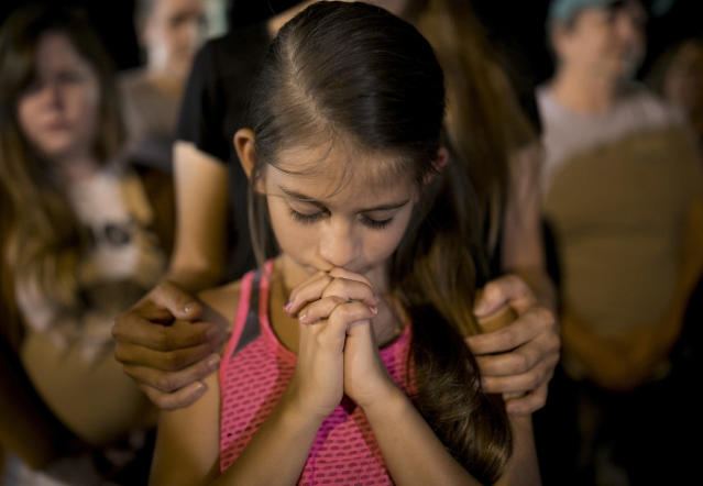 <p>Sophia Martinez, 9, prays at a memorial service for the victims of Sunday's church shooting in Sutherland Springs, Texas, Monday, Nov. 6, 2017. (Photo: Jay Janner/Austin American-Statesman via AP) </p>