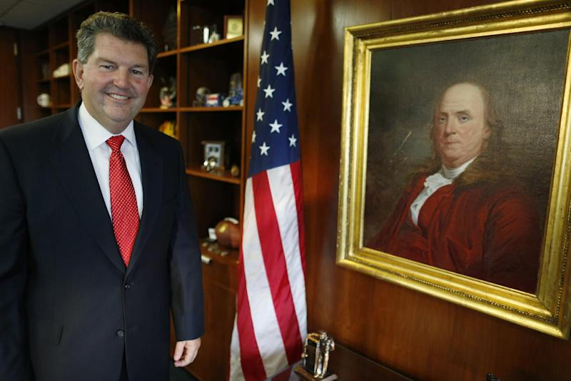 Postmaster General Patrick R. Donahoe poses with next to a portrait of Benjamin Franklin, the first postmaster general, after an interview with the Associated Press at his office at U.S. Postal Service Headquarters in Washington, Thursday, Aug. 1, 2013. Donahoe has a wish list for raising cash for his financially ailing agency. High on it is delivery of beer, wine and spirits. In an interview with The Associated Press, Donahoe also endorsed ending most door-to-door and Saturday mail deliveries as cost-saving measures. (AP Photo/Charles Dharapak)