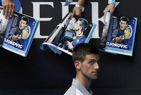 Novak Djokovic of Serbia walks past magazines featuring pictures of himself as he signs autographs after winning his men's singles match against Leonardo Mayer of Argentina at the Australian Open 2014 tennis tournament in Melbourne January 15, 2014. REUTERS/Jason Reed